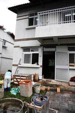 許多永久屋前堆滿了水泥預拌工具、木工器械、磁磚、地磚、水泥包,準備將新居改造成更符合他們需求的寓所
