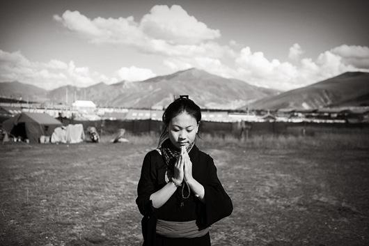 01 一位來自玉樹游牧地帶的藏族女子,雙手合十做出祈福手勢